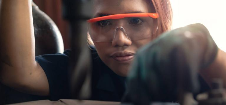 Female worker wearing safety glasses using a drill