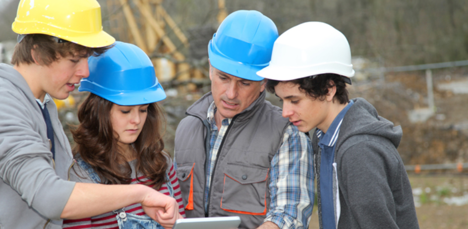 Adult with group of teenagers in professional training wearing construction hats.